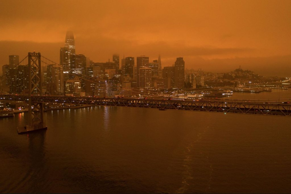 A suspension bridge-- the sky behind it is orange due to wildfires
